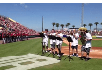 Members of the Detroit Symphony plays the National Anthem in Lakeland at a Grapefruit League game. It's a rite of Spring.